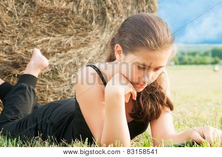 Girl With  Device Laying Close  To Haystack