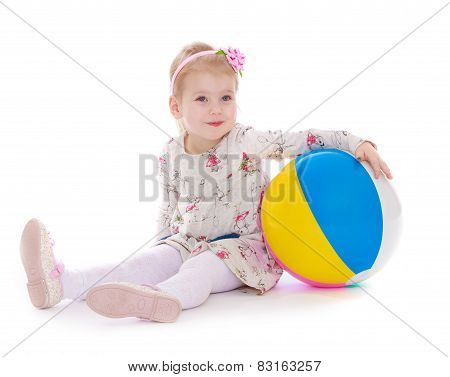 beautiful little girl sitting on the floor with a large sword in