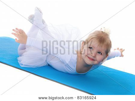 Happy joyful little girl athlete lying on a rug .. sports