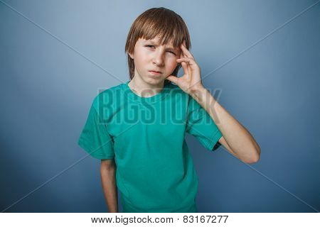 European-looking boy of ten years headache, migraine on a gray b