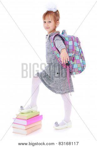 elegant beautiful schoolgirl with satchel on his back.