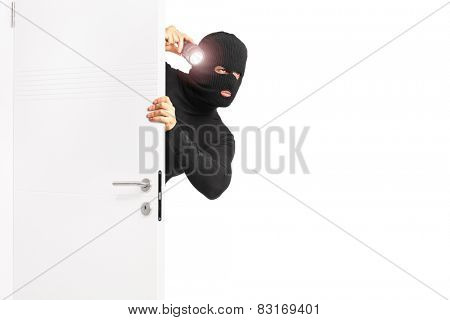 Burglar with flashlight entering through a door isolated on white background