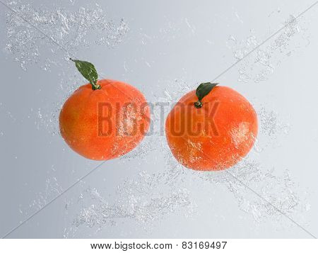 Two ripe orange clementines rich in vitamin c with water splash and bubble effect over a graduated grey background