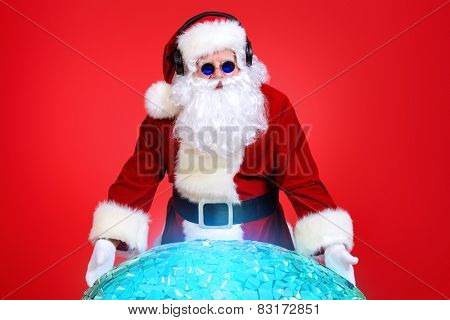 Santa Claus DJ near brilliant sparkling disco ball. Christmas celebration.