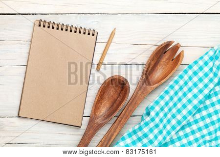 Notepad over kitchen towel and utensils on wooden table with copy space