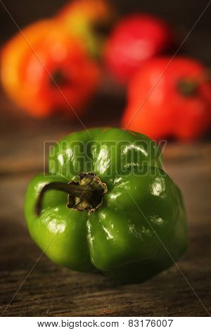 Green jamaican pepper on a rustic table with colorful peppers in a background