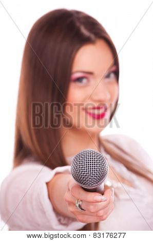 Young woman holding microphone, on white background with focus on the microphone