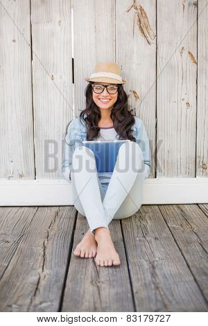 Pretty hipster sitting on ground with tablet against bleached wooden fence