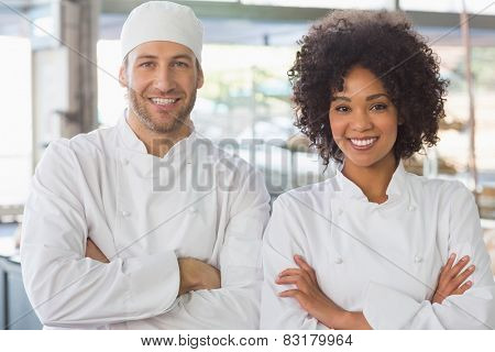 Team of bakers smiling at camera in the kitchen of the bakery