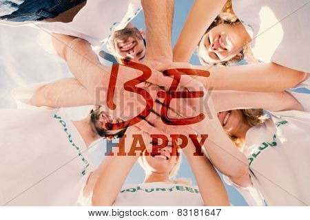 Happy volunteers with hands together against blue sky against be happy