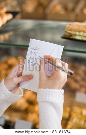 Woman checking her shopping list at the bakery