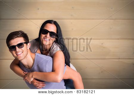 Man giving his pretty girlfriend a piggy back against bleached wooden planks background