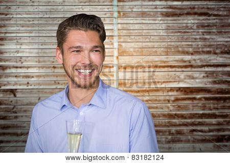 Man toasting with champagne against wooden planks