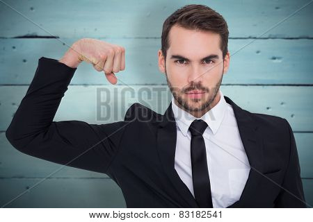 Businessman tensing arm muscle and looking at camera against painted blue wooden planks