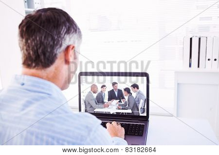 Man with grey hair using his laptop against business people disscussing a budget plan