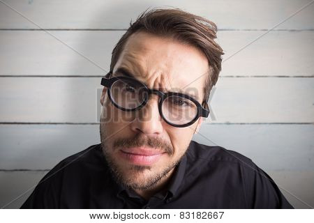 Portrait of a doubtful businessman with glasses against painted blue wooden planks