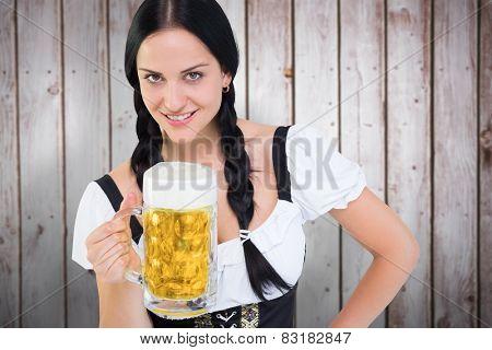 Pretty oktoberfest girl holding beer tankard against wooden planks