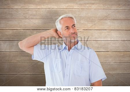 Thinking man posing with hand behind head against wooden surface with planks