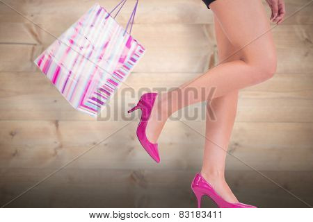 Womans legs in high heels against bleached wooden planks background