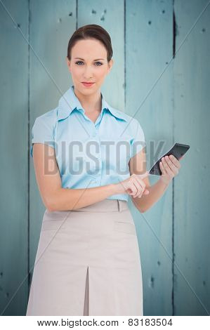 Serious classy businesswoman using calculator against painted blue wooden planks