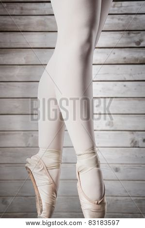 Ballerina standing en pointe against wooden planks
