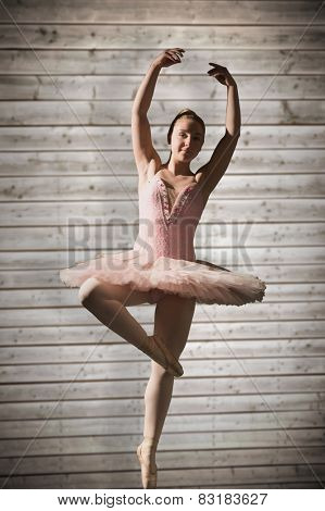 Pretty ballerina dancing against wooden planks background