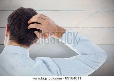 Businessman scratching his head against painted blue wooden planks