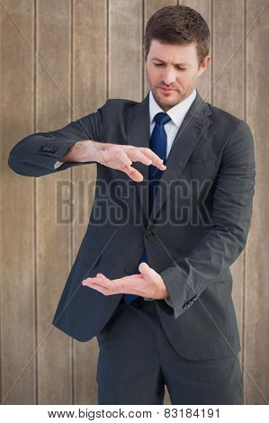Businessman showing something with his hands against wooden surface with planks