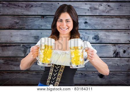 Pretty oktoberfest girl holding beer tankards against grey wooden planks