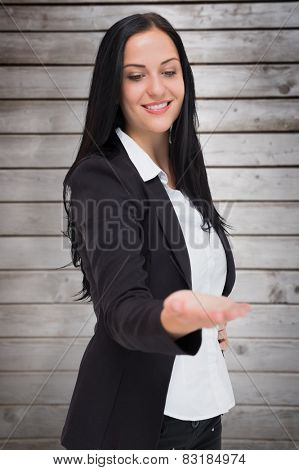 Pretty businesswoman presenting with hand against wooden planks