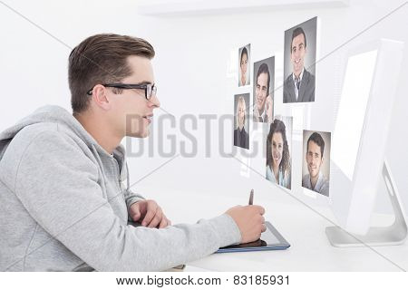 Casual man working at desk with computer and digitizer against profile pictures