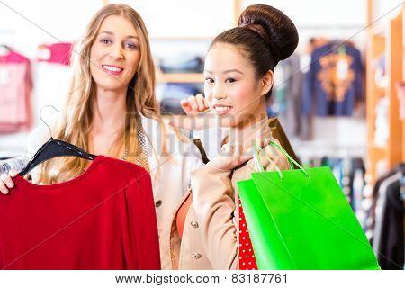 Women shopping in boutique or fashion store buying fashion, Asian and Caucasian friend