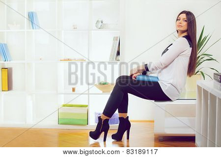 Happy smiling relaxing young woman in living room background.
