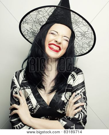 Funny Witch. Young happy woman with canival hat. Studio shot.