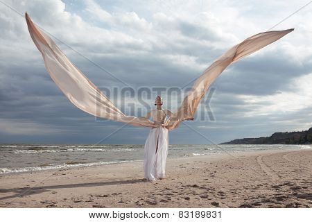 Female Model In Extreme Long Beige Dress Posing Dynamic In The Beach. Waving Fabric. Fluttering Long