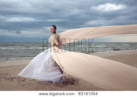 Fashionable Model With Extremely Long Dress Like A Wings. Vogue Style. Beautiful Model Walks At The
