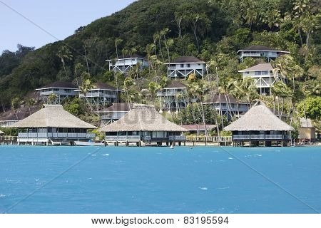 Hill by the sea and lodges on a slope. Polynesia.