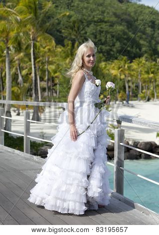 The young beautiful woman in a dress of the bride on the bridge about sea edge. Polynesia. Bora-Bora