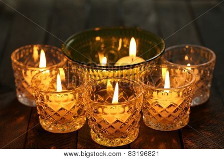 Burning candles in glass candlesticks close-up
