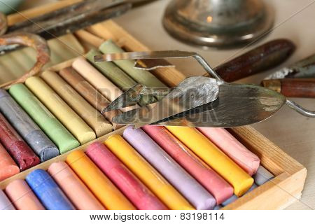 Colorful chalk pastels in box with palette knifes close up