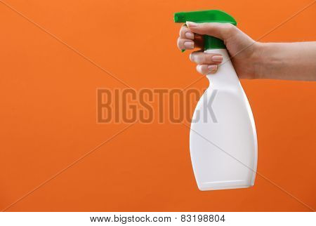 Male hand with sprayer on colorful background