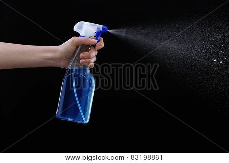 Male hand spraying water on black background
