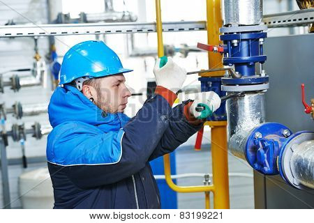 industrial heat engineer worker plumber at boiler room installation