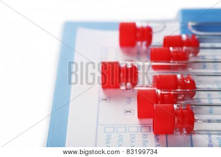 Test tubes and clipboard with medical history form close up
