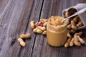picture of jar jelly  - Fresh made creamy Peanut Butter in a glass jar and peanuts on old wooden table - JPG