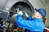 pic of auto repair shop  - car mechanic worker repairing brakes of lifted automobile at auto repair garage shop station - JPG