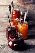 stock photo of jar jelly  - Jars of tasty jam on wooden background - JPG
