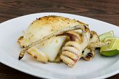 image of cuttlefish  - Grilled cuttlefish with lime on the wooden background - JPG
