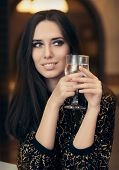 stock photo of flirty  - Portrait of a classical beauty toasting with a glass of champagne