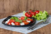 picture of black-cherry  - Italian Caprese salad with cherry tomatoes and baby mozzarella on black plate - JPG